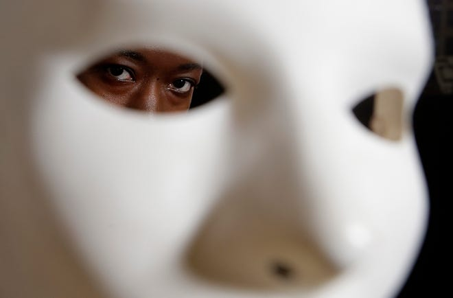 In this Wednesday, Feb. 13, 2019, photo, Massachusetts Institute of Technology facial recognition researcher Joy Buolamwini stands for a portrait behind a mask at the school, in Cambridge, Mass. Buolamwini's research has uncovered racial and gender bias in facial analysis tools sold by companies such as Amazon that have a hard time recognizing certain faces, especially darker-skinned women. Buolamwini holds a white mask she had to use so that software could detect her face. (AP Photo/Steven Senne)