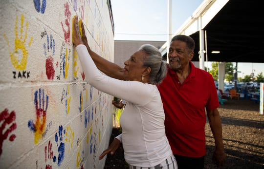 """Curtis and Carol Pearson of Detroit leave their handprints on the wall during the Art Park grand opening at Eastern Market on Thursday, July 18, 2019. """"I like to be around different cultures and people and enjoy the day,"""" Curtis Pearson said."""