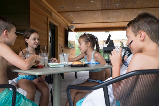 From left, Tristan Michael, 9, Hunter Peiser, 10, Sydney Peiser, 8 and Tinsley Michael, 9 all of Birmingham, grab a bite to eat on the balcony of the new Shark Tank at the Birmingham Athletic Club in Bloomfield Township, Mich., Thursday, July 18, 2019.
