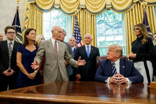 President Donald Trump listens to Apollo 11 astronauts Michael Collins, third from left, with Vice President Mike Pence and first lady Melania Trump.