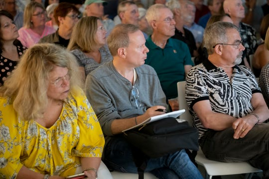 David Bloom, center, of the Birmingham Citizens for Responsible Government, listens during a community meeting about the new proposed parking structure.