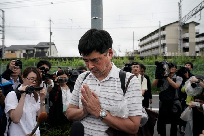 A man prays for the victims of Thursday's fire at the Kyoto Animation Studio building, Friday, July 19, 2019, in Kyoto, Japan.