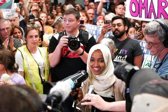 """U.S. Rep. Ilhan Omar speaks to supporters as she arrives at Minneapolis–Saint Paul International Airport, Thursday, July 18, 2019, in Minnesota. President Donald Trump is chiding campaign supporters who'd chanted """"send her back"""" about Somali-born Omar, whose loyalty he's challenged."""