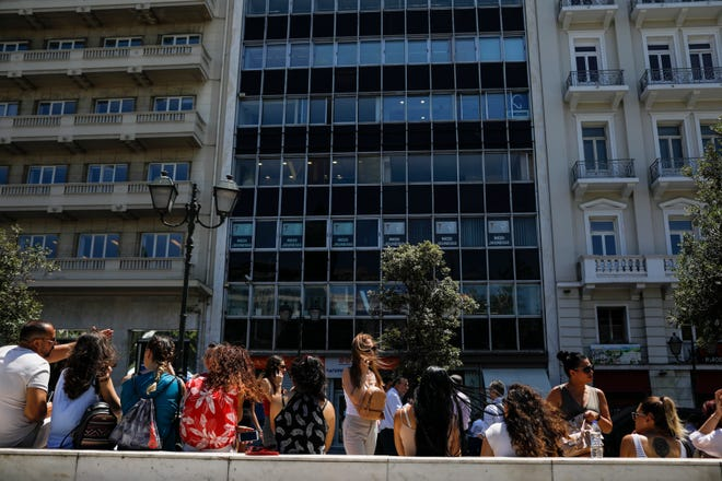 People speak on their phones as they stand outside the building they work in with the Greek Parliament in the background, after a strong earthquake hit near the Greek capital of Athens, Friday, July 19, 2019. The Athens Institute of Geodynamics gave the earthquake a preliminary magnitude of 5.1 but the U.S. Geological Survey gave it a preliminary magnitude of 5.3.