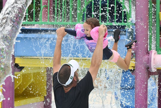 Al Beachum of Royal Oak lets his daughter CeCe fly through the cool water at Red Oaks Waterpark in Madison Heights on Friday.