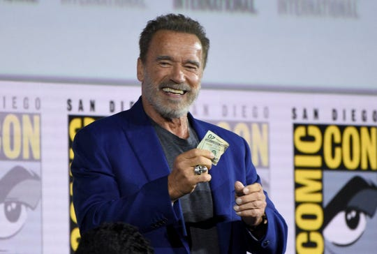 "Arnold Schwarzenegger gets twenty dollars after winning a bet to fellow cast member Diego Boneta at the ""Terminator: Dark Fate"" panel on day one of Comic-Con International on Thursday, July 18, 2019, in San Diego."