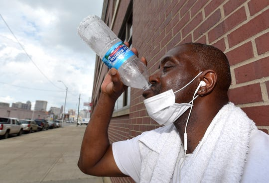 Detroiter David Morgan, a dock worker at the Salvation Army Detroit Warehouse, wears a towel around his neck as he takes a drink of ice water during a break along Fort Street on Friday afternoon.