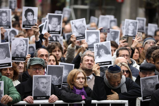 People hold up pictures of people who died during the bombing at the AMIA Jewish center that killed 85 people on the 25th anniversary of the attack in Buenos Aires, Argentina, Thursday, July 18, 2019.