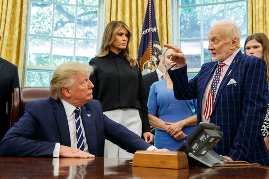 President Donald Trump listens to Apollo 11 astronaut Buzz Aldrin, right, with first lady Melania Trump.
