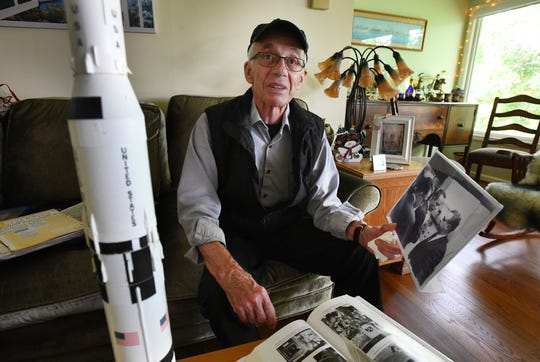 Electrical engineer Harlan Neuville, 88, who worked on the Apollo space program, holds a photo of himself with astronaut Alan Shepard and program director Jim Bevins, in Lake Orion.