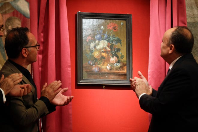 "German Foreign Minister Heiko Mass, left, and Italian Culture Minister Alberto Bonisoli watch the unveiling of the ""Vase of Flowers"" painting by Jan van Huysum, at the Pitti Palace in Florence, Italy, Friday, July 19, 2019."