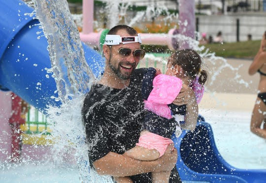 Al Beachum of Royal Oak splashes with his daughter CeCe at Red Oaks Waterpark in Madison Heights on Friday.