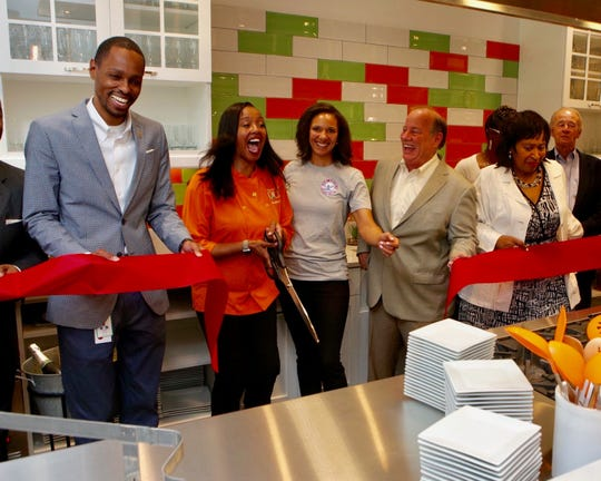 Chef and owner Quiana Broden, second from left, cuts celebrates the grand opening of her vegan cafe, the Kitchen, Friday morning in New Center with Pierre Batton of the DEGC, left, City Council President Pro‐Tempore Mary Sheffield, Mayor Mike Duggan and City Council President Jones Brenda Jones.