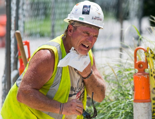 Jeff Neal with Blankenberger Brothers, Inc. wipes sweat from his face while he works on the Akin Park Storm Sewer Project as the Tri-State reached 94 degrees under an excessive heat warning Friday, July 19, 2019.