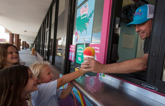 McKenna Gardner, 5, of Cape Coral, receives a Rainbow SnoBall from Paul Everhart, owner of Pelican's SnoBalls Myers.