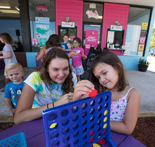 Abby Graff, 15, and Genevieve Currier, 4, play a game of Connect 4 at Pelican's SnoBalls in North Fort Myers.