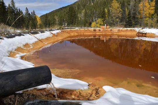 FILE - In this Oct. 12, 2018, file photo, water contaminated with arsenic, lead and zinc flows from a pipe out of the Lee Mountain mine and into a holding pond near Rimini, Mont. An appeals court Friday, July 19, 2019, has sided with the Trump administration after it dropped a proposal that would have required mining companies to prove they have the wherewithal to clean up future pollution. (AP Photo/Matthew Brown, File)