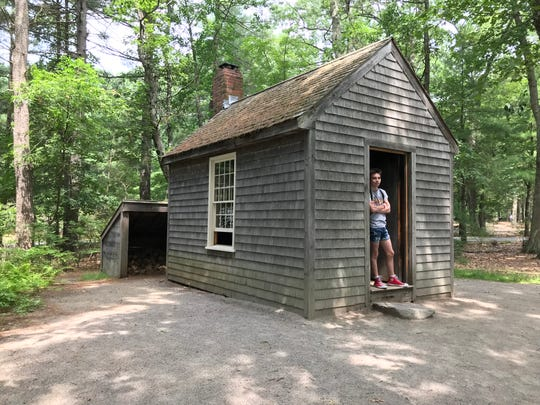 Harrison Jenkins leans against the doorframe of a re-creation of the cabin where American essayist, poet, and philosopher Henry David Thoreau lived in during his two years, two months and two days at Walden Pond near Concord Massachusetts.