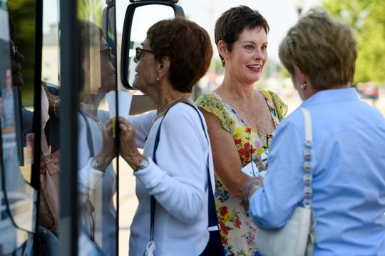 Dana Harvey, center, with the Henderson Tourist Commission, offers visitor guides to people hopping on one of several American Queen Steamboat Company tour buses in downtown Henderson Friday. The steamboat visitors were offered a handful of pit stops around the area, including to John James Audubon State Park and the Henderson Brewing Co.