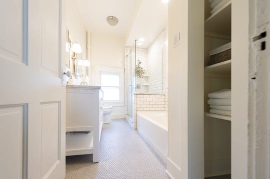 The full bath on the second floor has been generously upgraded with bright-white tiles, glass tile flooring and bright fixtures. This home, built in 1870, is situated in the heart of Johnson County's county seat, Franklin, Thursday, July 18, 2019.