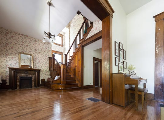 The home's foyer opens up to the living room, stairwell, hallway and a sitting area with one of the home's three fire places. This home, built in 1870, is situated in the heart of Johnson County's county seat, Franklin, Thursday, July 18, 2019.