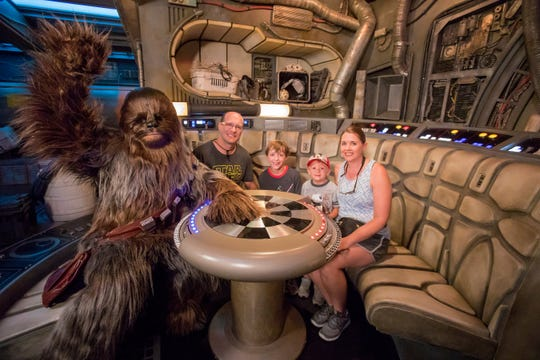 Eight-year-old Jonathan Ridgeway of Ocean Springs, Mississippi (center, back) becomes the one millionth guest to take to take the controls of Millennium Falcon: Smugglers Run at Star Wars: Galaxy's Edge at Disneyland Resort in Anaheim, Calif., Tuesday, July 16, 2019. Chewbacca joined (l-r) Rodger Ridgeway, Jonathan Ridgeway, 8, Logan Ridgeway, 4, and Becky Ridgeway for a photo. The family was welcomed in the Main Hold of Millennium Falcon with a surprise declaration, which included a visit by Chewbacca, followed by the ride experience and toasting blue and green milk with his family. This significant milestone comes just weeks since the land opened.  (Joshua Sudock/Disneyland Resort)