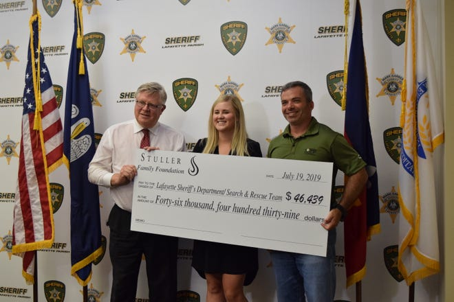 Executive Director of the Stuller Family Foundation Scott Brazda (left) and board member Alex Graham present a check to Lafayette Parish Sheriff Mark Garber for the the department's Search and Rescue Team on July 19, 2019.