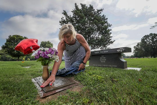 Michele Crockett, mother of Max Gilpin, uses some water and a shirt to wipe off her son's grave on what would have been Gilpin's 26th birthday. He died after becoming overheated at football practice at Pleasure Ridge Park High School. July 19, 2019