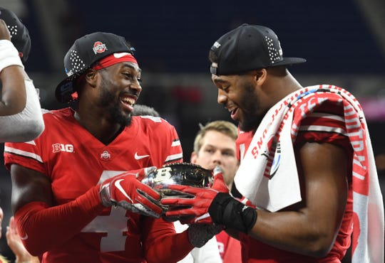 Ohio State safety Jordan Fuller (left) and defensive end Jonathon Cooper celebrate with the 2018 Big Ten title trophy after beating Northwestern. A rematch between the two teams is set for Friday night.