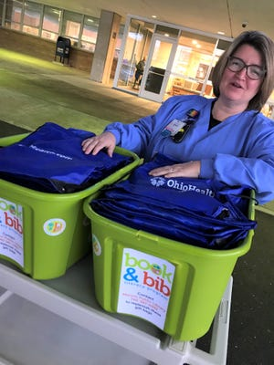 Shannon Pressley, health unit coordinator at OhioHealth, stands with the Book & Bib program gift bags that will go to parents of newborns to encourage family reading.