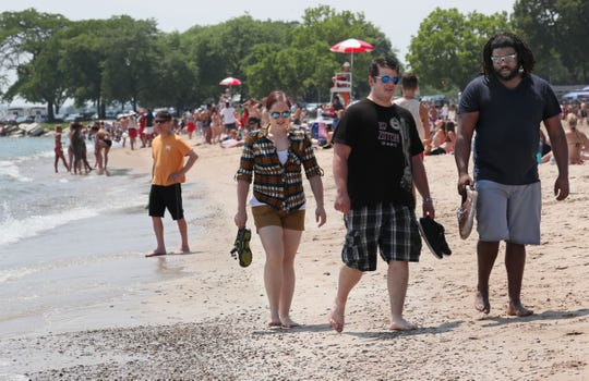 Sarah Boyd, left, and Harley Miller, center, both of St. Louis, Missouri, get a tour of Milwaukee, including the beach, from Andrew Triplett of Milwaukee on Friday.