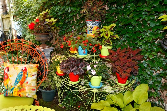Assorted potted and climbing plants add color and interest to this shady spot in the garden.