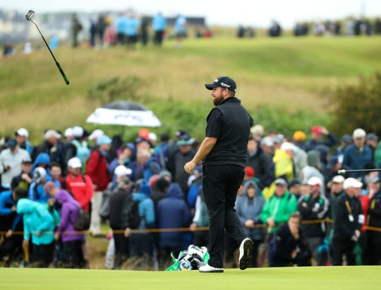 Co-leader Shane Lowry throws his putter to his caddie on the 14th green after suffering the first of only two bogeys for the Irishman during the second round of the British Open on Friday at Royal Portrush.