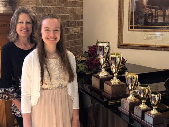 Heather Spencer (second from left) displays her five Gold Cup Trophy while pictured with her her piano teacher, Mrs. Caryl Reddick.