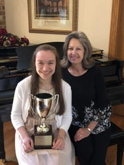 Heather Spencer (left) is shown with her piano teacher, Mrs. Caryl Reddick, after receiving her Grand Cup Trophy.