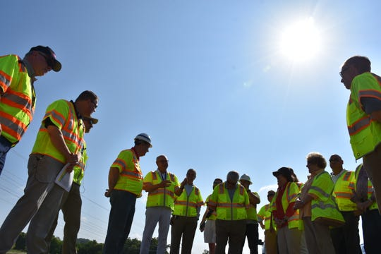 Around a dozen elected officials gathered on the construction site of Mack Hatcher Memorial Parkway to tour on July 19, 2019.