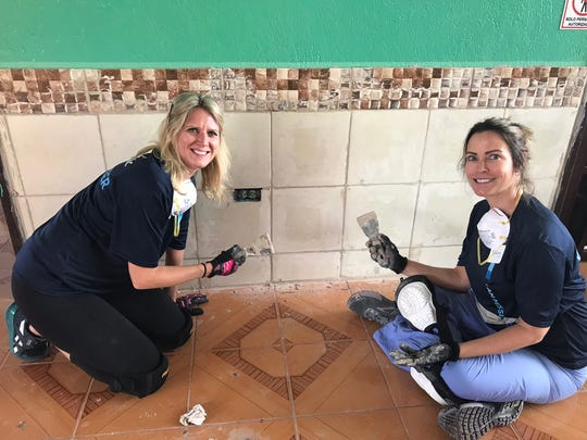 Becky Fox, left and Sandy Hickey, right, grout tile in Ecuador.