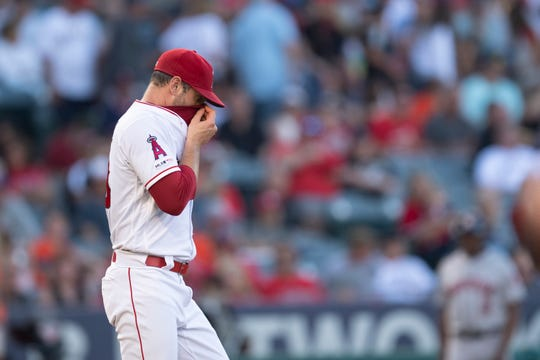 Los Angeles Angels starting pitcher Matt Harvey wipes his sweat after giving up a home run to Houston Astros' George Springer in a baseball game in Anaheim, Calif., Thursday, July 18, 2019.