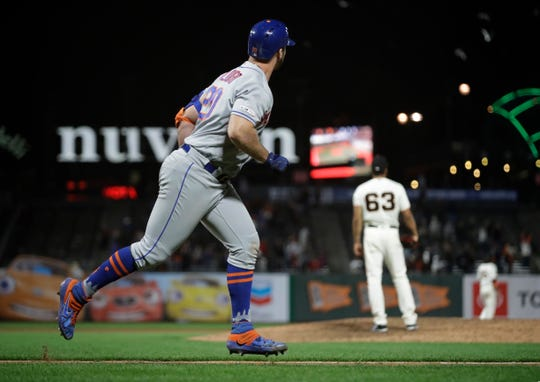 New York Mets' Pete Alonso, left, watches his home run off San Francisco Giants' Williams Jerez (63) in the 16th inning of a game Thursday, July 18, 2019, in San Francisco.