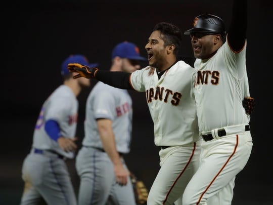 San Francisco Giants' Donovan Solano, second from right, celebrates with first base coach Jose Alguacil, right, after making the game winning hit in the 16th inning of a baseball game Thursday, July 18, 2019, in San Francisco.