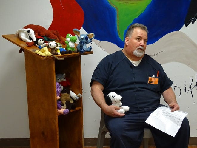 An Otero County Detention Center inmate sits with a Snoopy doll he crocheted as part of the Otero County Prison Facility Crochet Program.