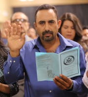 A man pledges an oath to the United States during a naturalization ceremony, Friday July 19, 2019, at the Las Cruces Convention Center.