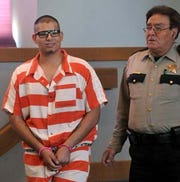 Irvin Ramirez enters District Judge Jerald Valentine's courtroom in this file photo as he is escorted by court security Larry Trujillo. Ramirez was sentenced to life in prison for killing Adam Espinoza, not including an additional years for other charges related to the crime.