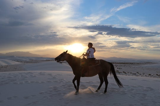 Gov. Michelle Lujan Grisham rides a horse at sunset at White Sands National Monument July 18.