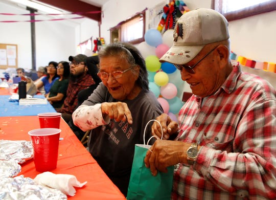 Bessie Napoleon, left, reacts to Edward Smith winning a door prize at a luncheon on July 18 to recognize the elderly and veterans at the Gadii'ahi-To'koi Chapter house.