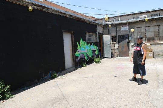Arrow Soul Trading Post owner Luke Paul examines a blank wall where a mural will be painted in the Hidden Garden events space off West Main Street in downtown Farmington.