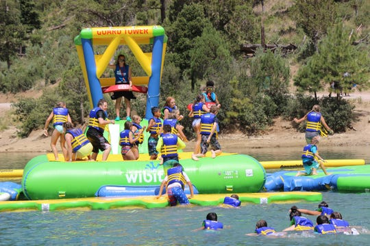 Members of the Ruidoso Boys and Girls club race governor Lujan-Grisham to the Wibit at Grindstone Lake.