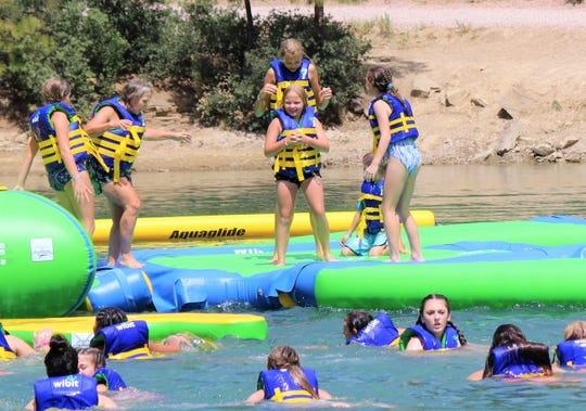 Governor Lujan-Grisham and the Ruidoso Boys and Girls Club have fun goofing around on the Wibit Water PArk on Grindstone lake during the  governor's visit to the Village of ruidoso.