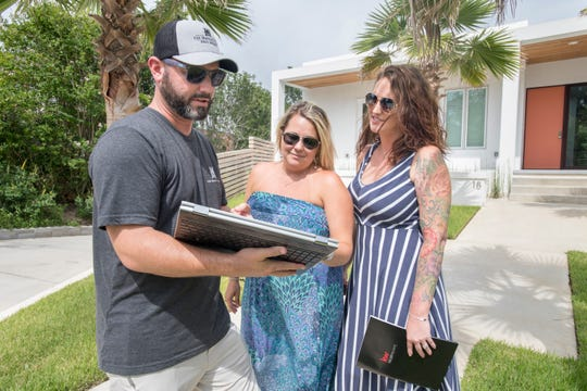 At left, Erik Hansen, a real estate agent with Keller Williams Realty Gulf Coast, shows fellow real estate agents Angela Greco and Courtney Howell a house for sale on Shoreline Place in Gulf Breeze on July 19.