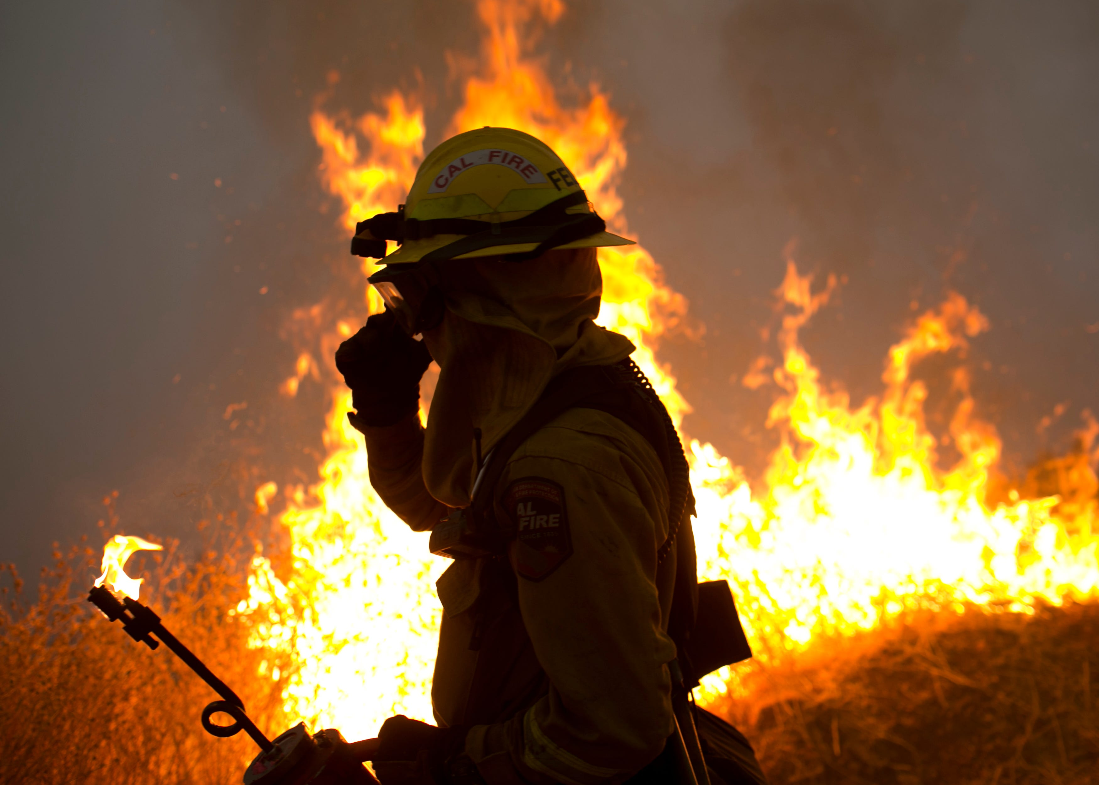A firefighter helps ignite a controlled burn in an attempt to halt the Camp Fire on Nov. 14, 2018.